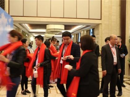 工作人员给经销商们带上红围巾